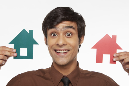 Businessman holding up two cut out houses, smiling Stock Photo - 22635811