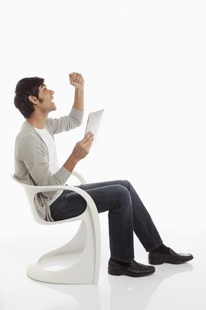 Man using a digital tablet, cheering Stock Photo