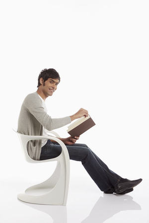 Man reading a book while sitting photo