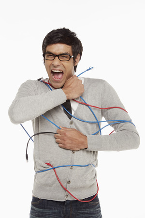 freeing: Man freeing himself from tangled network cables
