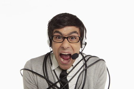 cable tangle: Man with headset wrapped in a tangled cable Stock Photo
