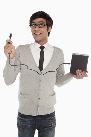 Man holding up an external hard disc photo