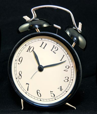 royalty free: time passing on black alarm clock isolated on black background