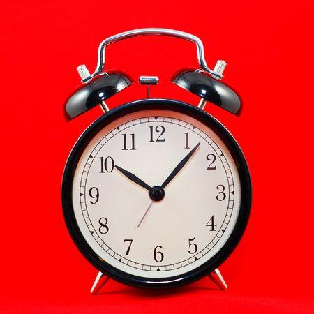 black alarm clock isolated on red background  photo