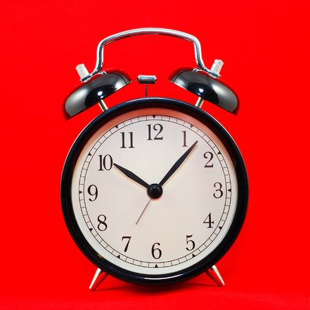 royalty: black alarm clock isolated on red background
