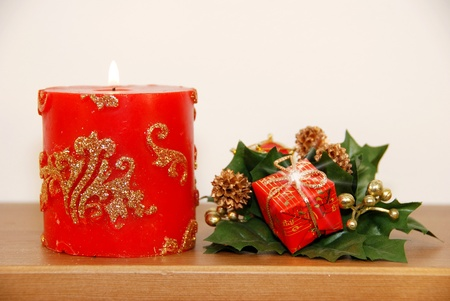 Cristmas arrangement with candle and petite gifts photo