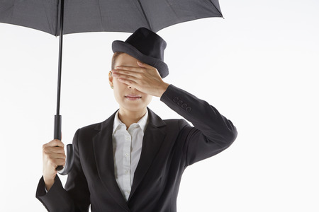 Businesswoman covering her eyes while standing under the umbrella photo