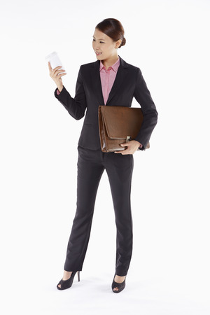 Businesswoman holding a disposable cup and a briefcase photo