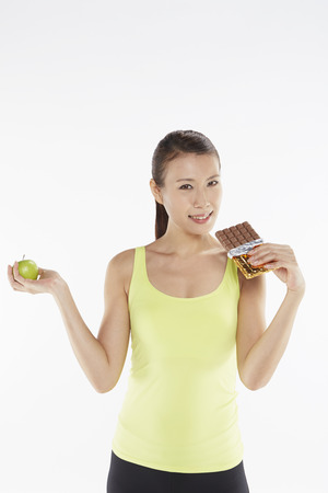 Woman deciding between an apple and a chocolate bar photo