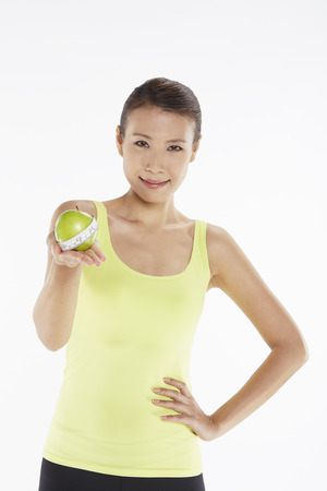 Woman holding a green apple and a weight scale photo