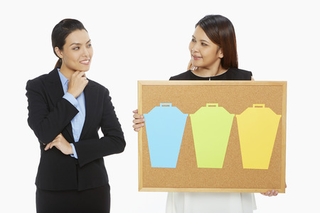 contemplates: Woman holding up a pin board while the other contemplates