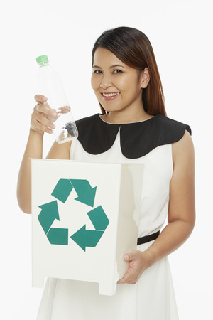 Cheerful woman discarding a plastic bottle into a recycle bin photo