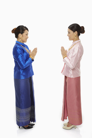 Women in traditional clothing greeting one another
