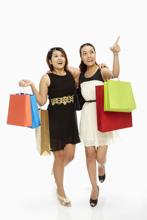 Cheerful women carrying paper bags and smiling photo
