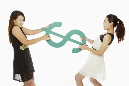 Two women pulling a dollar sign photo