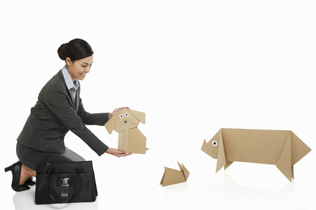 Businesswoman holding up a paper dog photo