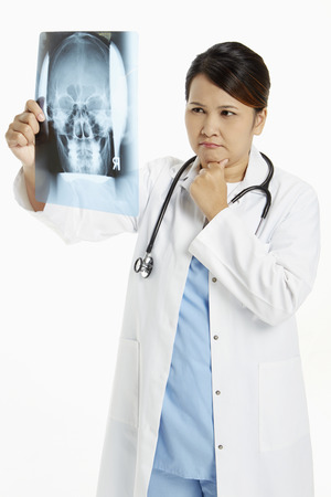 Medical personnel examining an x-ray film