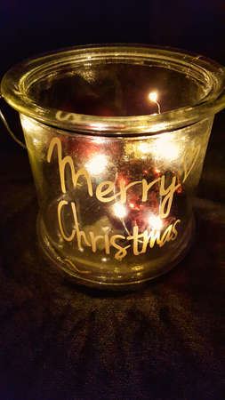 some illuminated christmas tree balls in a jar with dark background and the inscription MERRY CHRISTMAS