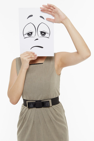 sad face: Woman holding up a sad face doodle