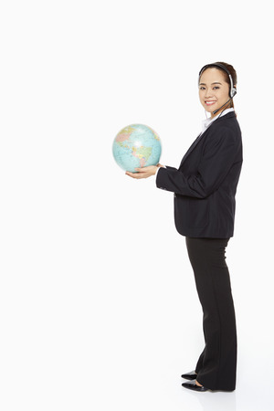 Businesswoman with headset holding a globe photo