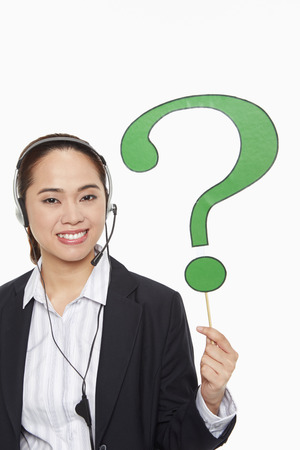 Businesswoman with headset holding up a question mark symbol photo