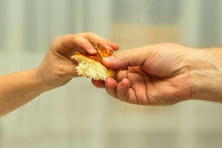 2 つの手は、パンの一部を渡す、背景がぼやけています。