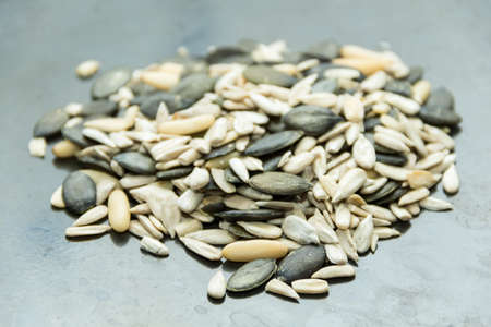 Sunflower seeds, pumpkin seeds, nuts of the Korean pine decomposed into a heap, close up photo