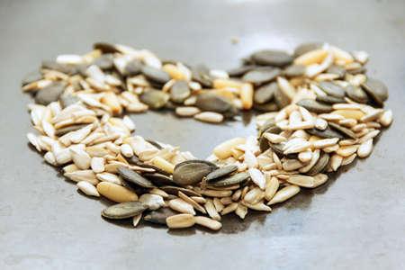 decomposed: Las semillas de girasol, semillas de calabaza, nueces del pino coreano descompuestos en un mont�n en forma de coraz�n Foto de cerca Foto de archivo