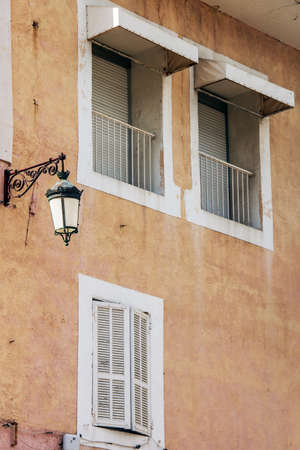 close p: the lantern on the house, two balconies, window, old house pink building the picture up close, in the daytime Stock Photo