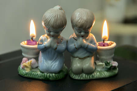 two lighted candlesticks distributed as ceramic candlesticks figure girl and boy photo