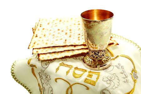 pesaj: los s�mbolos de la fiesta de la Pascua; tres piezas de pan �cimo; vidrio; tela blanca con bordados y la fuente en la Pesach hebreo; sobre un fondo blanco; aislado Foto de archivo