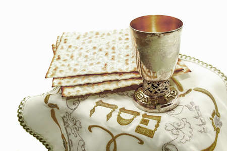 the symbols of the feast of Passover, three pieces of matzah, glass, white cloth with embroidery and font on the Hebrew Pesach, on a white background, isolated