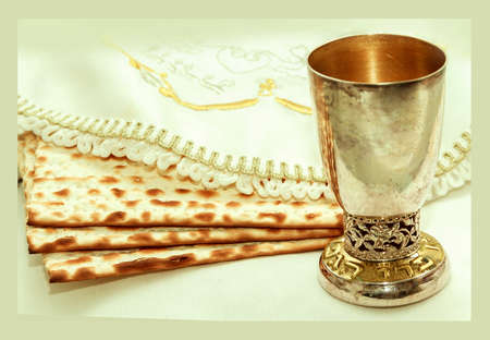 the feast of the passover: the symbols of the feast of the Passover, matzah, a cup with wine and font in Hebrew, white cloth with embroidery, white background, isolated