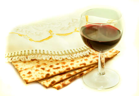 the feast of the passover: the symbols of the feast of Passover, three pieces of matzah, poured a glass of red wine, white cloth with embroidery and font on the Hebrew Pesach, on a white background, isolated