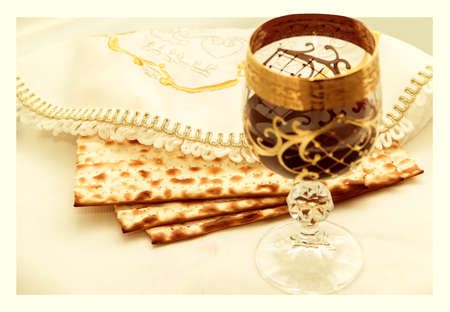 kiddush: the symbols of the feast of Passover, three pieces of matzah, poured a glass of red wine, white cloth with embroidery and font on the Hebrew Pesach, on a white background, isolated