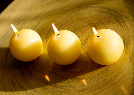 table surface: three round, burning candles, and the shiny surface of the table