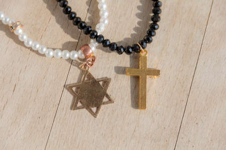 zionism: Two pearl necklaces, one with the cross, another star of david with the star-six-corners, on wooden background