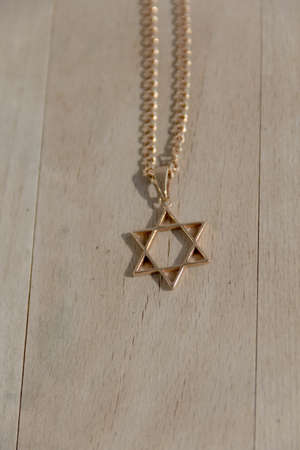 zionism: chains, gold six-cornered star, with the trailer of the Star of David, on the wooden background