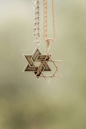 zionism: two chains, a gold six-cornered star, another silver with the trailer of Star of David Stock Photo