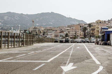 lifespan: Road with arrows on the pavement, boat, dock, car ride, mountain Stock Photo