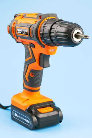 Cordless combination drill for use as a conventional drill, automatic screwdriver. Combined drill close-up on a blue background, vertical photo. Selective focus