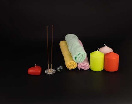 Spa composition with candles, aroma sticks dark background. Wellness, relax massage and body treatment concept.