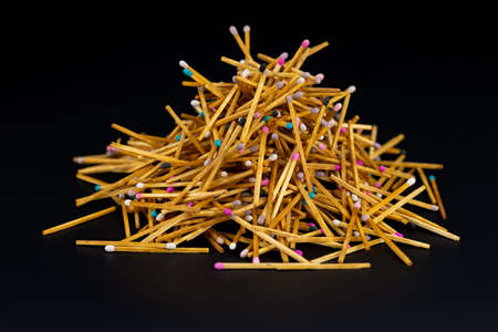 a lot of matches are lying on a black background. selective focus