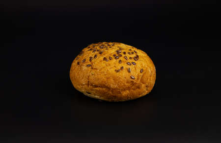 Round white baked bun soft fresh with crispy crust sprinkled with sesame seeds for fast food on a black background