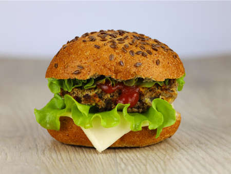 Delicious fast food, hamburger, hamburger, cheeseburger, bun witch sesam and with cheese, beef cutlet, salad and ketchup, on a wooden background