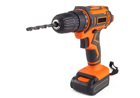 Electric drill with a drill bit. A screwdriver on the battery. Isolated on a white background, close-up.
