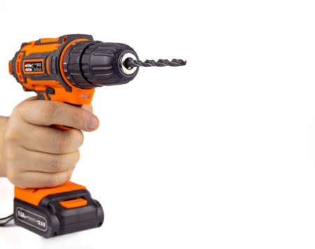 Electric drill with a drill bit in hand. A screwdriver on the battery. Isolated on a white background, close-up, selective focus. 免版税图像