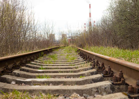 Abandoned railway in the forest, factory chimneys in the distance. Selective focus.