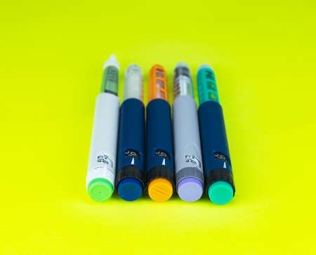 Different colored insulin syringe pens for insulin therapy on green background. Close-up, selective focus. 免版税图像