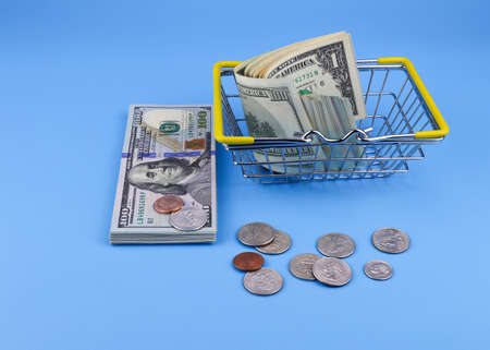 Shopping cart and paper dollars on a blue background.